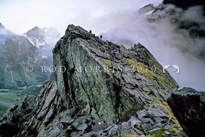 11011-22018 Fiordland scenery. Rock climbers on Homer Saddle *