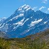 sunshine strikes snow-capperd Mount Cook byond valley below