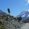 Hiker stands on pile of rocks beside Hookers Valley Track looking to Mount Cook