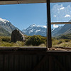 Window view in old trampers hut in mountains, on the Hookers Track, Mount Cook in New Zealand s Southern Alpine region.