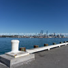 Auckland skyline and port with container cranes on other side of harbour with Devonport wharf and white bollard in foreground.