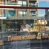Barber and patron through venetian blind window with street reflections around sign Dan's Traditional Barber shop and Shave Parlour on Karangahape Road.