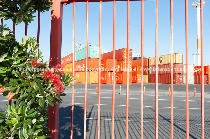 Large waterfront yard of Ports Of Auckland with stacks of containers and port handling equipment through bright orange fence.