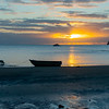 Silhouette of dinghy at waters edge at low tide on Mulberry Grove Beach