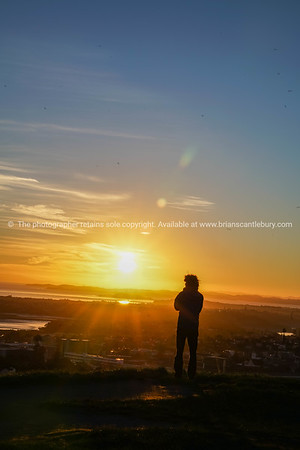 Auckland city skyline and Sky Tower beyond shadowed Mount Eden at sunrise.