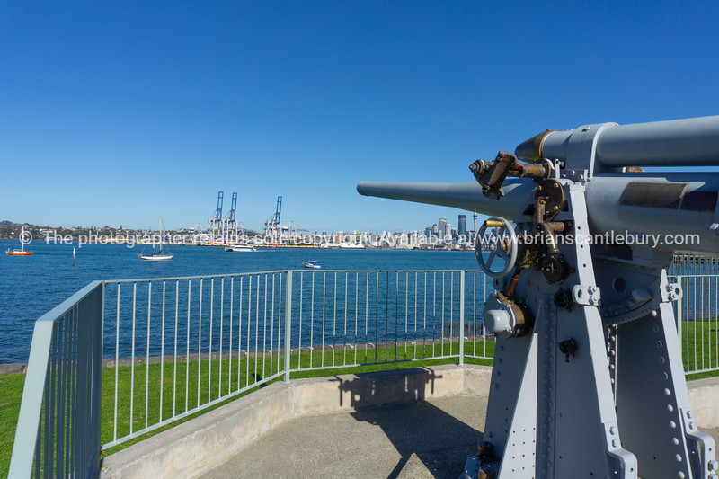 An old machine gun on display by  Naval base in Devonport  with Auckland city skyline across harbor.