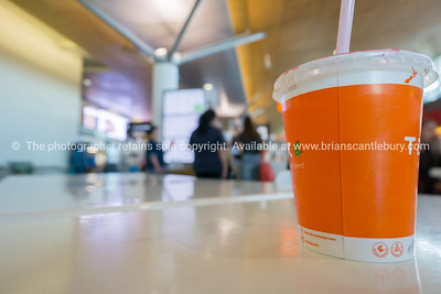 Orange drink cup against defocused background