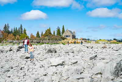 tourists  clambering over rocks enjoy experience of rocky foreshore