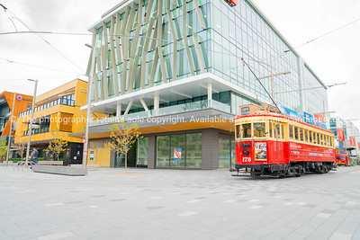 Number 178 City Tour tram passes new buildings in business district