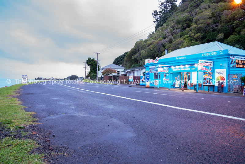 Bright blue Tararu Store at dawn on cloudy morning on State Highway north of Thames.