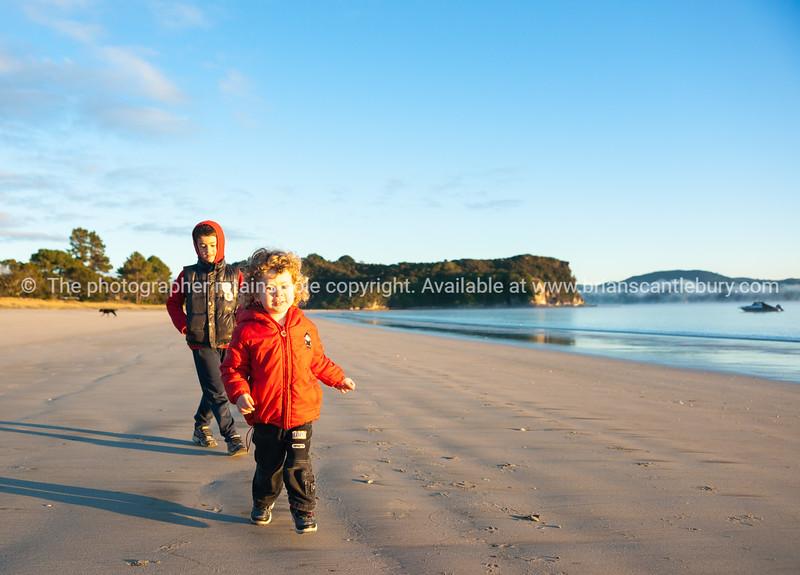 Small boys running on beach in winter.