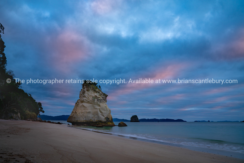 Beach at Cathedral Cove on the Coromandel under colorful overcast sky.