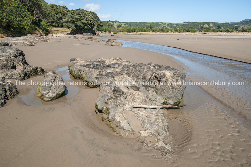 Creeks winds across beach to sea at Hicks Bay. New Zealand images.