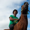 Young Maori man in green shirt riding brown horse along beach.