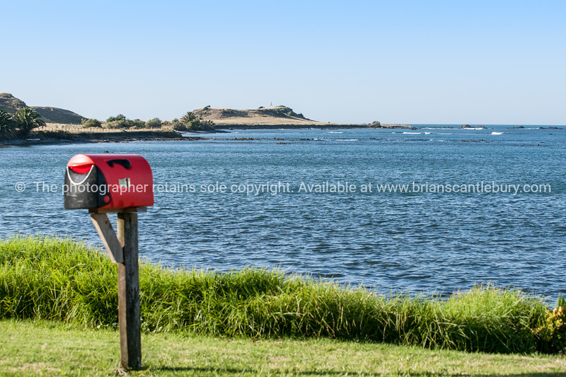 Red letterbox, Waihau Bay.  New Zealand images.