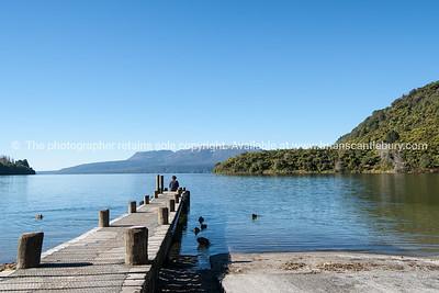 Woman sits on end of Lake Tarawera jetty.