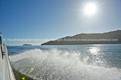 Sun bursts over Marlborough Sounds as boat skims across the bay. New Zealand Stock images.