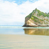 Large rock left after ages of erosion of -shore Wharaiki Beach