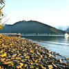 Rocks on a Punga Cove Beach pick up first golden ray of sun. New Zealand Image.