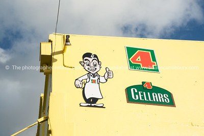 New Zealand icon, Four Square man and logo on yellow wall. New Zealand image.
