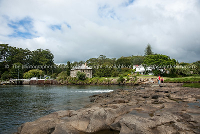 Historic Stone Store with people crossing the causeway from other side of harbour.Northland