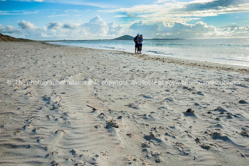 Karikari beach beachcombers with Puwheke in distance. New Zealand images.