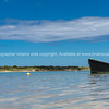 Blue dinghy afloat on peaceful calm Ngunguru estuary Northland New Zealand