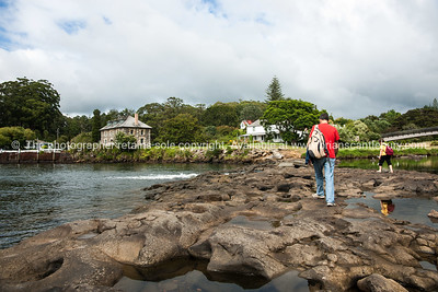 Historic Stone Store with people crossing the causeway from other side of harbour.Northland. Northland