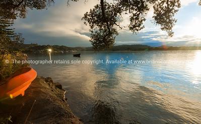 Orange kayak on waters edge of peaceful calm estuary at sunrise on overcast morning with light under tree hitting kayak Ngunguru Northland New Zealand