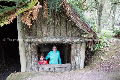 Children look out window of Maori home in Tarawera Buried Village.