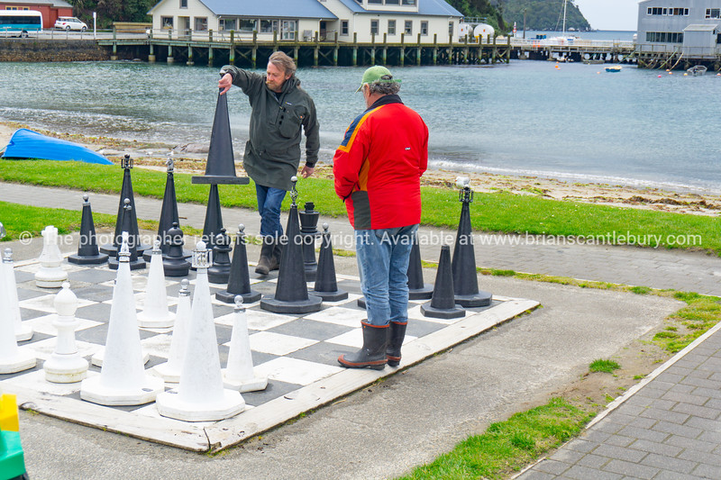 Chess players on oversized outdoor board and set.