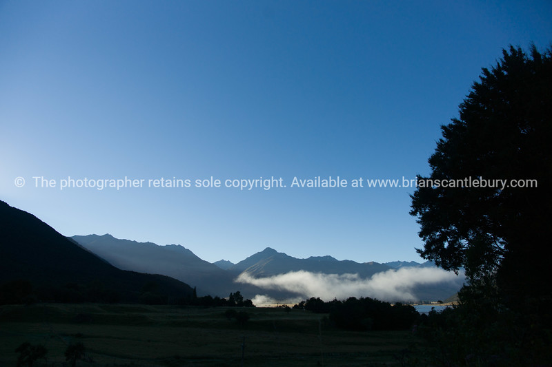 Low cloud hovers above the land, below surrounding hills at Paradise, Glenorchy.