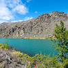 Clutha River with sun on scenic grassy slopes and turquoise rive