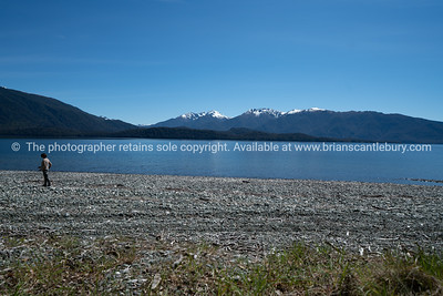 Blue Lake Te Anau and sky separated by snowcapped mountains