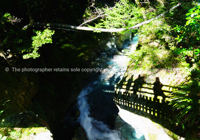 South Island Scenic. Trampers shadows on ravine wall, above river.