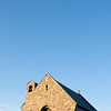 Sun sets on stone front of Church of Good Sheppard in Tekapo.