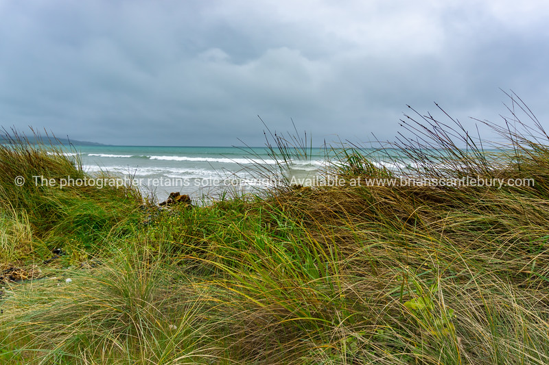 Windy overcast day with view out to horizon at Colac Bay in southern New Zealand coastal background.