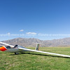 Glider resting on airfield surrounded by mountains of South Island