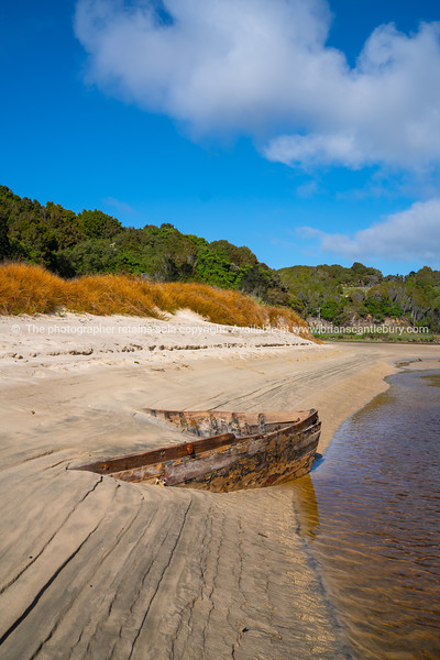 Lines and patterns curving along edge of stream interupted by bow of old wooden boat  stuck in sand