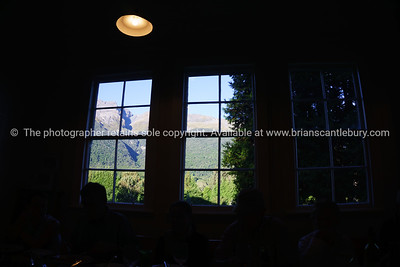 Southern Alps through windows of old school room at Paradise, the interior silhouetted against the outdoor environment.