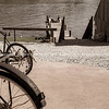 Old bicyle wheels in street in small town with group four youth in distance on jetty