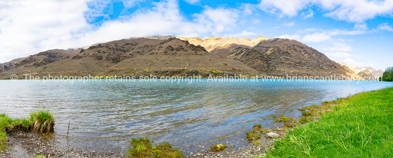 River banks flowing water and hills on other side of scenic Clutha River