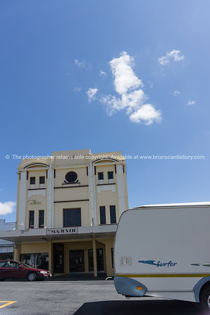 Car and caravan pass in street in front of 1917 Majestic Theatre in Taihape, New Zealand