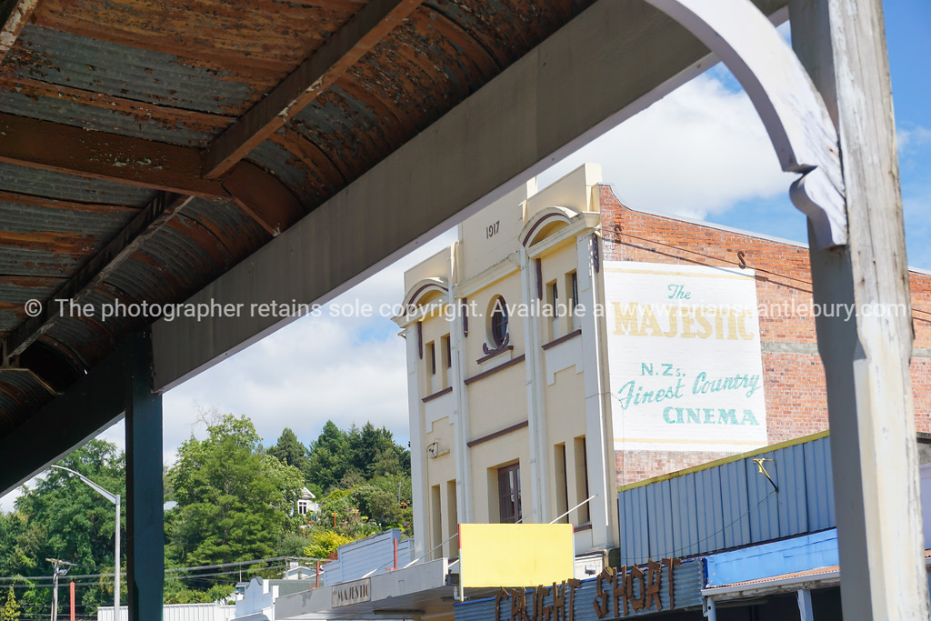 Old faded Majestic Theatre sign on brick wall from unders veranda across road on Taihape Building
