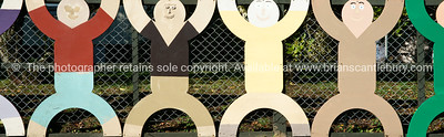 Row of cut-out children on fence.