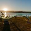 "Sun sets across lake and the Art sculpture along the Lake Terrace. Lake Taupo named ""Swell""."
