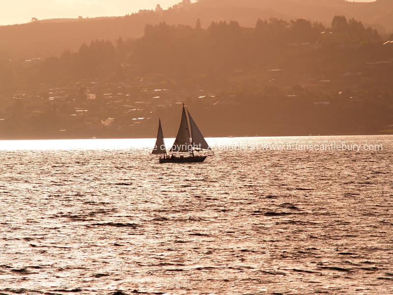 Yacht back lit by setting sun.