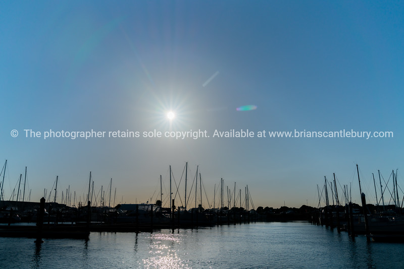 Boats moored in marina backlit by rising morning sun