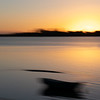 Impressionist coastal motion blur sunrise with dinghy on beach