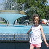 Small girl by fountain showing enjoyment and splashing in Tauranga Memorial Park.